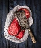 Carne de vaca cruda con la cuchilla de carne vieja en fondo de madera azul marino Imágenes de archivo libres de regalías