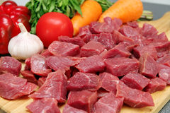 Carne de vaca cruda del corte con las verduras en la placa de madera Imagen de archivo