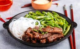 Carne de vaca picante frita con las semillas de sésamo, las habas verdes y los tallarines de arroz imágenes de archivo libres de regalías