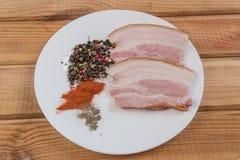 Carne del bacon con le spezie delle spezie su una tavola di legno immagine stock