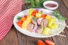 Carne del Bbq en los palillos, pinchos del kebab con la salsa, en backgrou de madera imagenes de archivo