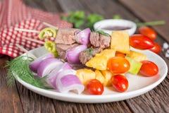 Carne del Bbq en los palillos, pinchos del kebab con la salsa, en backgrou de madera foto de archivo