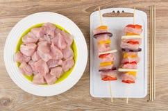 Carne del pollo en placa y shashlik en los pinchos en la tabla de madera Fotografía de archivo