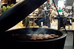 Carne deliciosa que asa a la parrilla con las llamas y el humo abastecimiento en comida Fotos de archivo