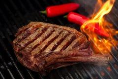 Carne dell'alimento - bistecca di manzo sulla griglia del barbecue del bbq con la fiamma Fotografie Stock