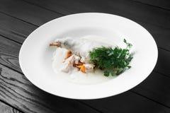 Carne di coniglio stufata in panna acida sul piatto bianco Fotografia Stock