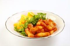 Carne di maiale affettata brasata con le arance sul piatto bianco Fotografia Stock