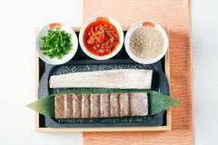 Carne di maiale affettata con la salsa e la cipolla di peperoncino rosso sul bento immagini stock