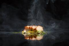 Carne di maiale affettata su fondo nero con fumo fotografia stock