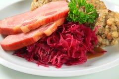 Carne di maiale affumicata con gli gnocchi tirolesi e il kraut rosso Fotografia Stock