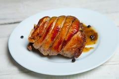 Carne di maiale arrostita isolata sul piatto bianco Articolazione fumata ed arrostita di carne di maiale su fondo luminoso Immagine Stock Libera da Diritti