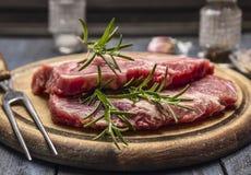 Carne di maiale cruda con i rosmarini su un bordo di legno con una forcella, fine su immagine stock
