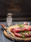 Carne di maiale cruda con i rosmarini su un bordo di legno con una forcella, fine su immagine stock libera da diritti