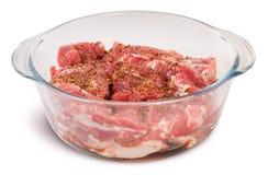 Carne di maiale cruda con le spezie in una ciotola di vetro Immagini Stock Libere da Diritti