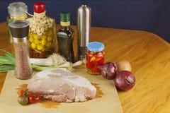 Carne di maiale cruda fresca su un tagliere con le verdure Fotografie Stock Libere da Diritti