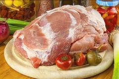 Carne di maiale cruda fresca su un tagliere con le verdure Immagini Stock Libere da Diritti
