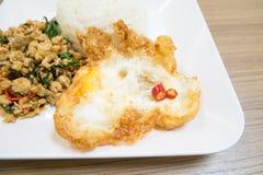 Carne di maiale e basilico in padella tailandese ed uovo fritto fotografia stock
