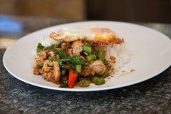 Carne di maiale ed uovo fritti piccanti su riso Fotografia Stock