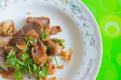 Carne di maiale fritta con aglio sul piatto bianco Fotografia Stock