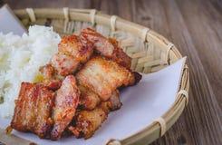 Carne di maiale fritta nel grasso bollente con riso appiccicoso sul canestro di legno, alimento tailandese, tailandese Fotografia Stock