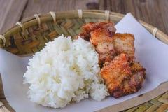 Carne di maiale fritta nel grasso bollente con riso appiccicoso sul canestro di legno, alimento tailandese, tailandese Fotografie Stock