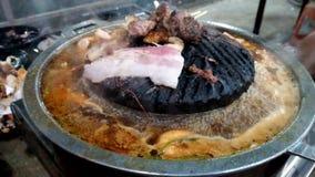 Carne di maiale grigliata su una pentola che sta bruciando dal calore e dal gamberetto in minestra d'ebollizione con molto fumo stock footage