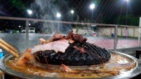 Carne di maiale grigliata su una pentola che sta bruciando dal calore e dal gamberetto in minestra d'ebollizione con molto fumo video d archivio