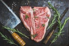 Carne di marmo fresca cruda della bistecca con l'osso sui precedenti rustici immagini stock libere da diritti