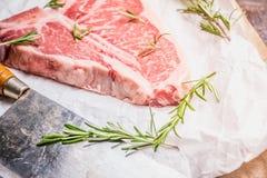Carne di marmo fresca cruda della bistecca con l'osso sui precedenti rustici fotografia stock