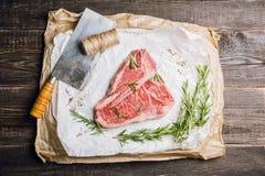 Carne di marmo fresca cruda della bistecca con l'osso sui precedenti rustici fotografie stock libere da diritti