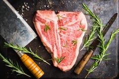 Carne di marmo fresca cruda della bistecca con l'osso sui precedenti rustici immagine stock libera da diritti