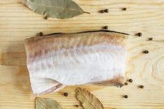 Carne di pesce con il primo piano della spezia Piselli del pepe e foglia di alloro per condire Vista superiore su fondo di legno Immagine Stock Libera da Diritti