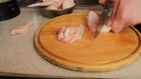 Carne di pollo del cuoco delle mani del ` s degli uomini Il coltello taglia la carne del ` s del pollo su un perno di legno stock footage