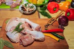 Carne di pollo grezza su una bugia del tavolo da cucina, delle verdure e degli accessori della cucina vicino fotografie stock
