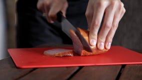 Carne di taglio La ragazza taglia i pezzi di carne affumicata cruda sul bordo Primo piano stock footage