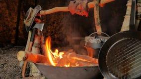 Carne di torrefazione su un bastone mentre cocendo pane in un forno olandese sopra un fuoco di accampamento archivi video