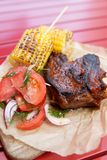 Carne do BBQ com milho e os tomates grelhados fotografia de stock