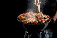 Carne do churrasco do homem em um assado portátil foto de stock