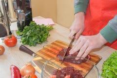 Carne do corte do cozinheiro chefe na placa de corte Cozinheiro chefe no trabalho, cozinha Imagens de Stock Royalty Free