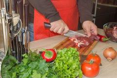 Carne do corte do cozinheiro chefe na placa de corte Cozinheiro chefe no trabalho, cozinha Fotografia de Stock Royalty Free