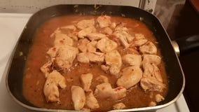 A carne do frango frito é fritada no molho de soja em uma frigideira video estoque