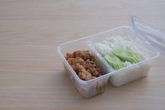 Carne e arroz do frango frito em uma caixa pl?stica imagem de stock