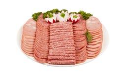 Carne e più del prosciutto del salame sul piatto isolato sulla parte posteriore di bianco Fotografia Stock
