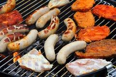 Carne e salsiccie su una griglia Fotografie Stock