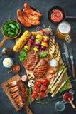 Carne e vegetais grelhados na placa de pedra rústica Imagens de Stock Royalty Free
