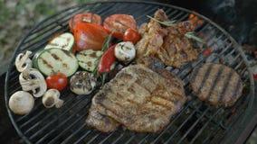 Carne e vegetais na grade com fogo e no fumo no fundo, um prato do restaurante, carne no osso, carne branca vídeos de arquivo