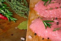 Carne ed erbe piccanti sui precedenti di legno Immagine Stock