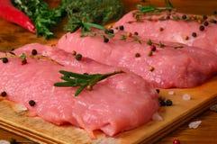 Carne ed erbe piccanti sui precedenti di legno Immagini Stock Libere da Diritti