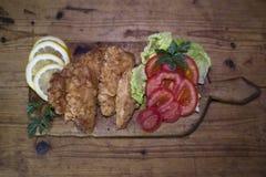 Carne empanada del pollo con la ensalada y el limón que descansan sobre un Wo rústico Imagen de archivo libre de regalías