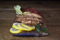 Carne empanada del pollo con la ensalada y el limón que descansan sobre un Wo rústico Foto de archivo